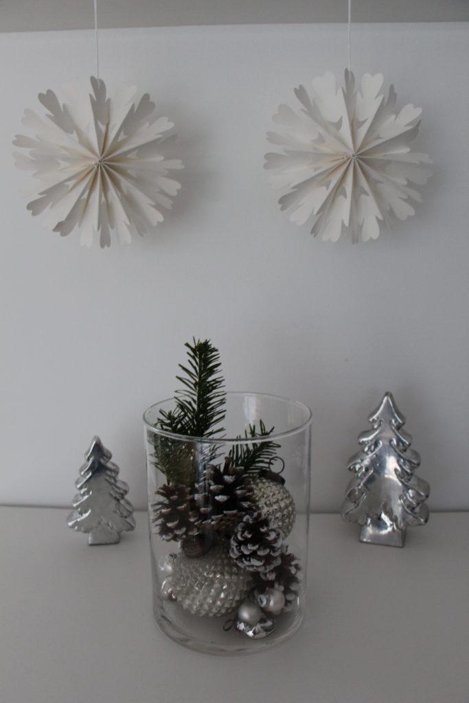 Adventsdekoration mit silbernen Kugeln und Tannenbäumen